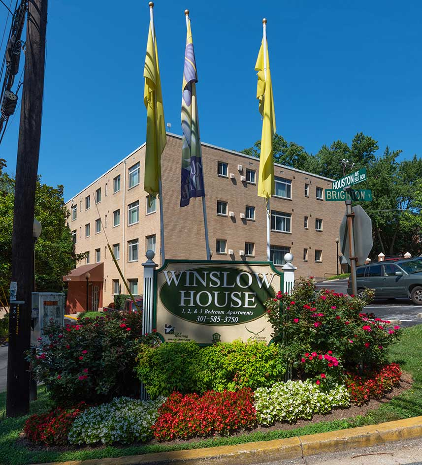 Welcome sign to Winslow House apartments surrounded by red flower bushes and shrubs