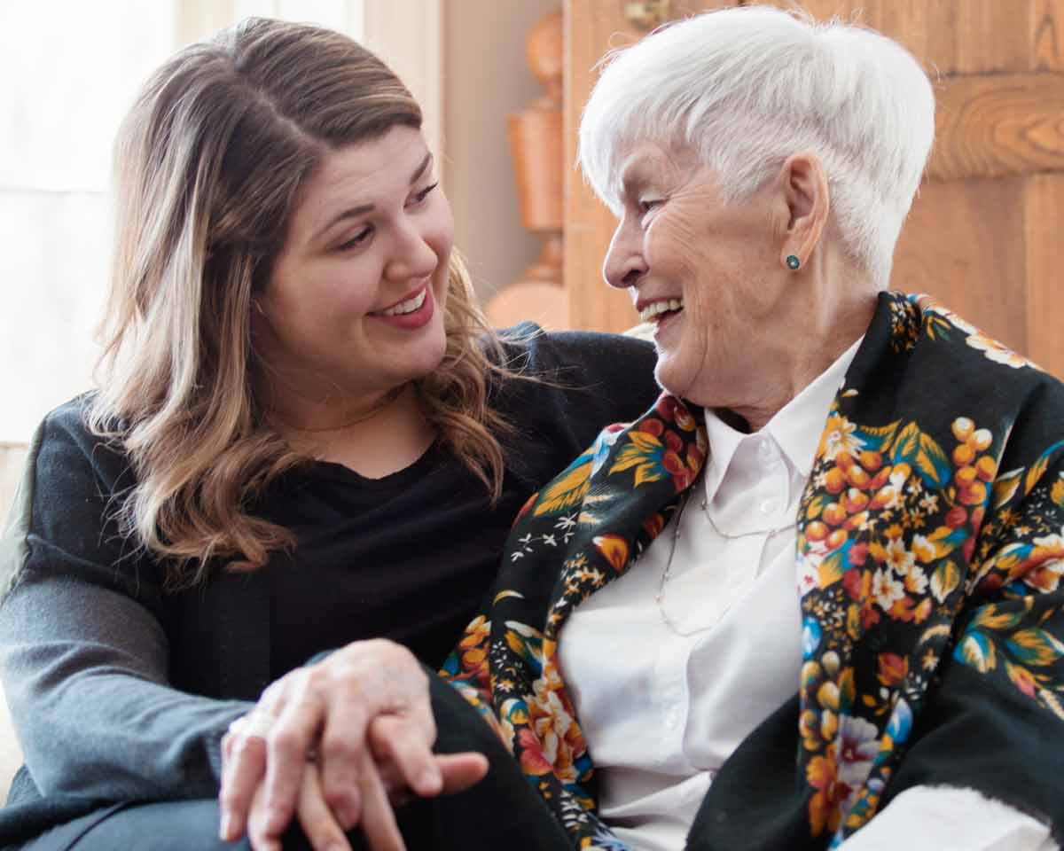 Young woman and older woman sit closely together and smile at each other