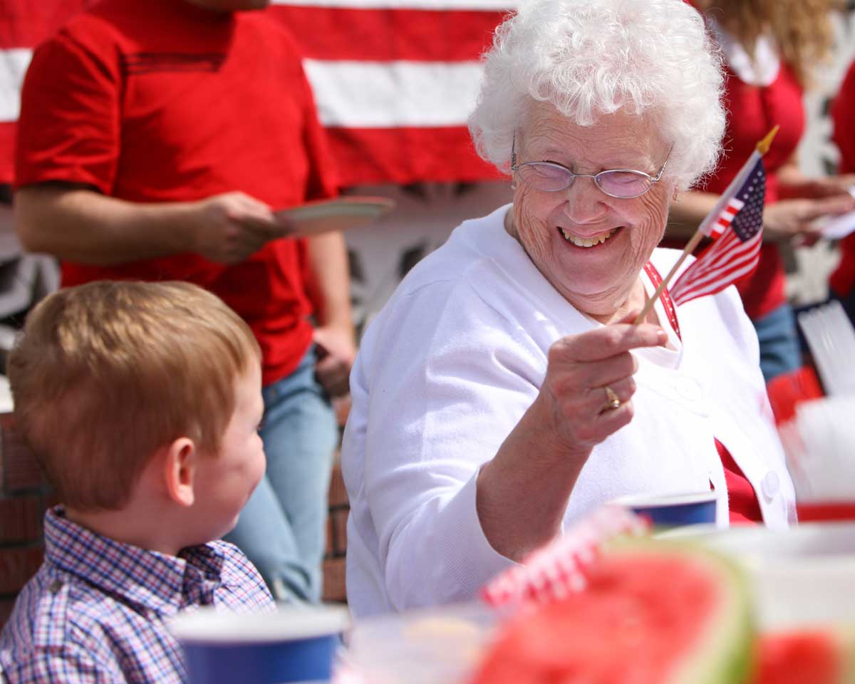 Older woman and young boy wave American flags together at an outdoor patriotic event