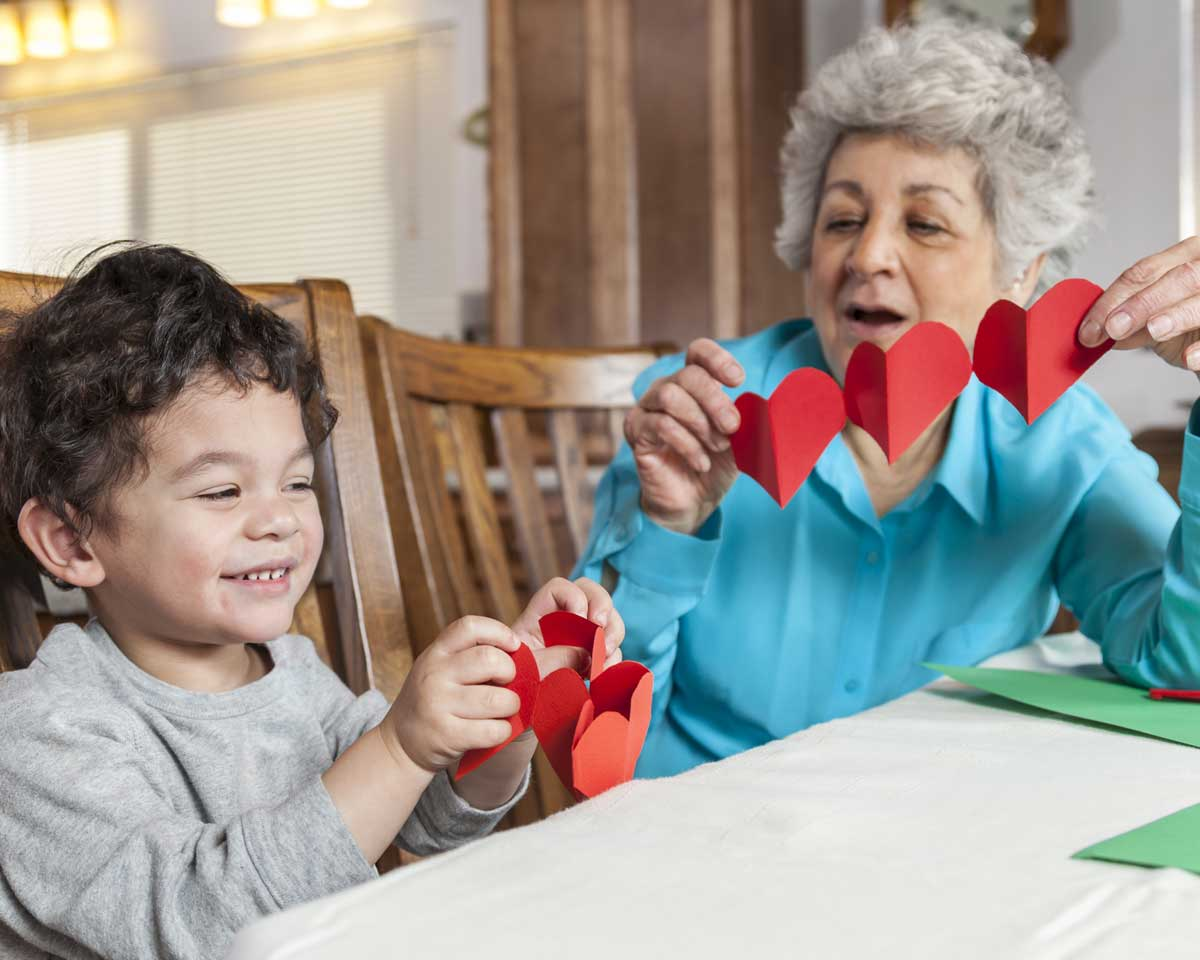 An image of a Malta House resident and their grandkid. They are making cutout red hearts together.