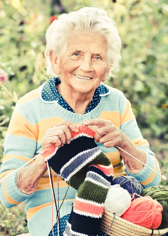 Older woman in striped sweater sits and knits in front of flower garden area with basket of yarn in lap