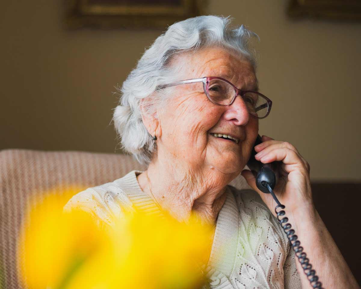 Older woman wearing glasses smiles while talking on landline telephone