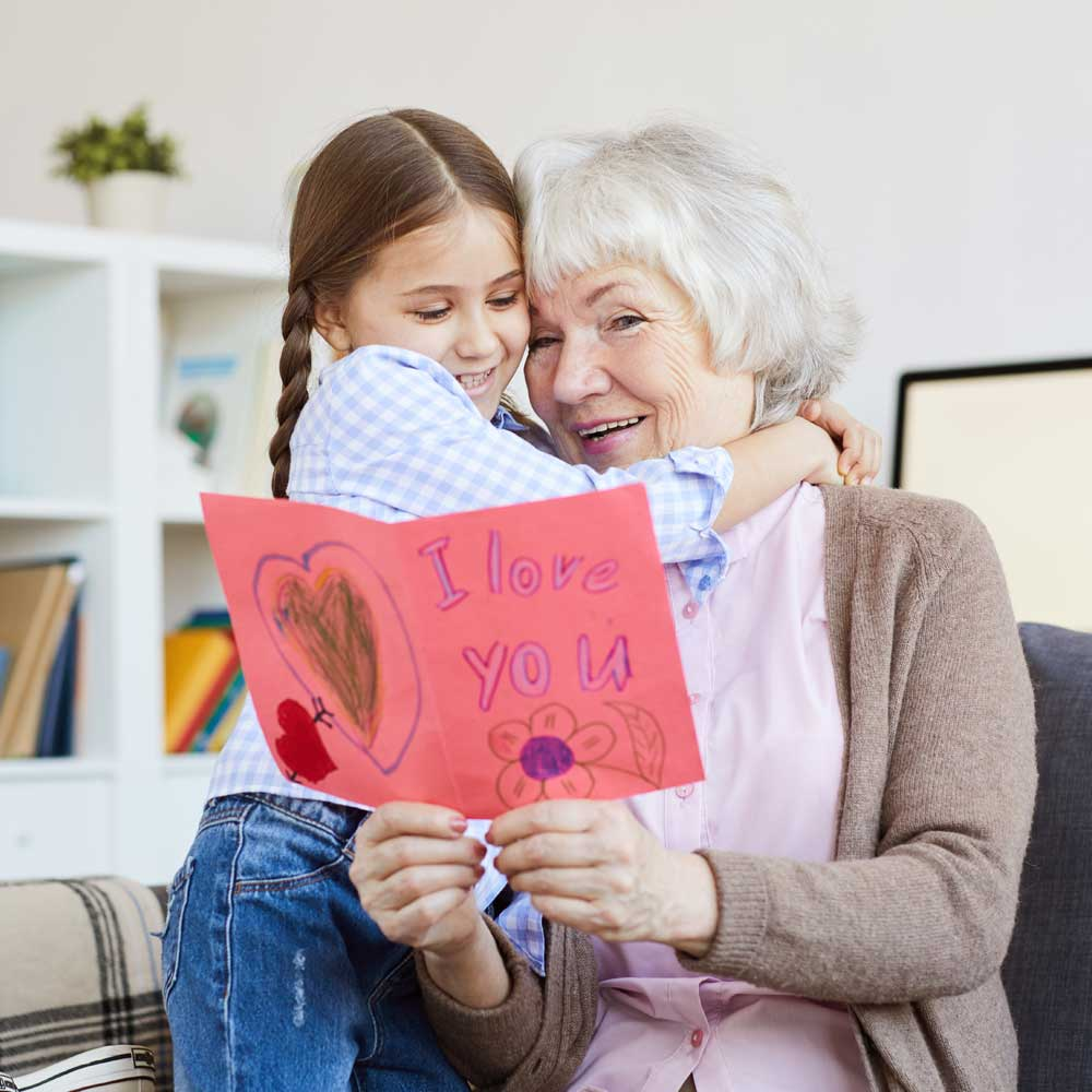 """Older woman receives hug and handmade card featuring words """"I love you"""" from young girl"""