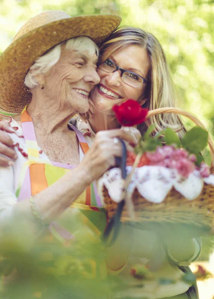 Older woman in straw hat and middle-aged woman hug while holding basket of flowers from garden