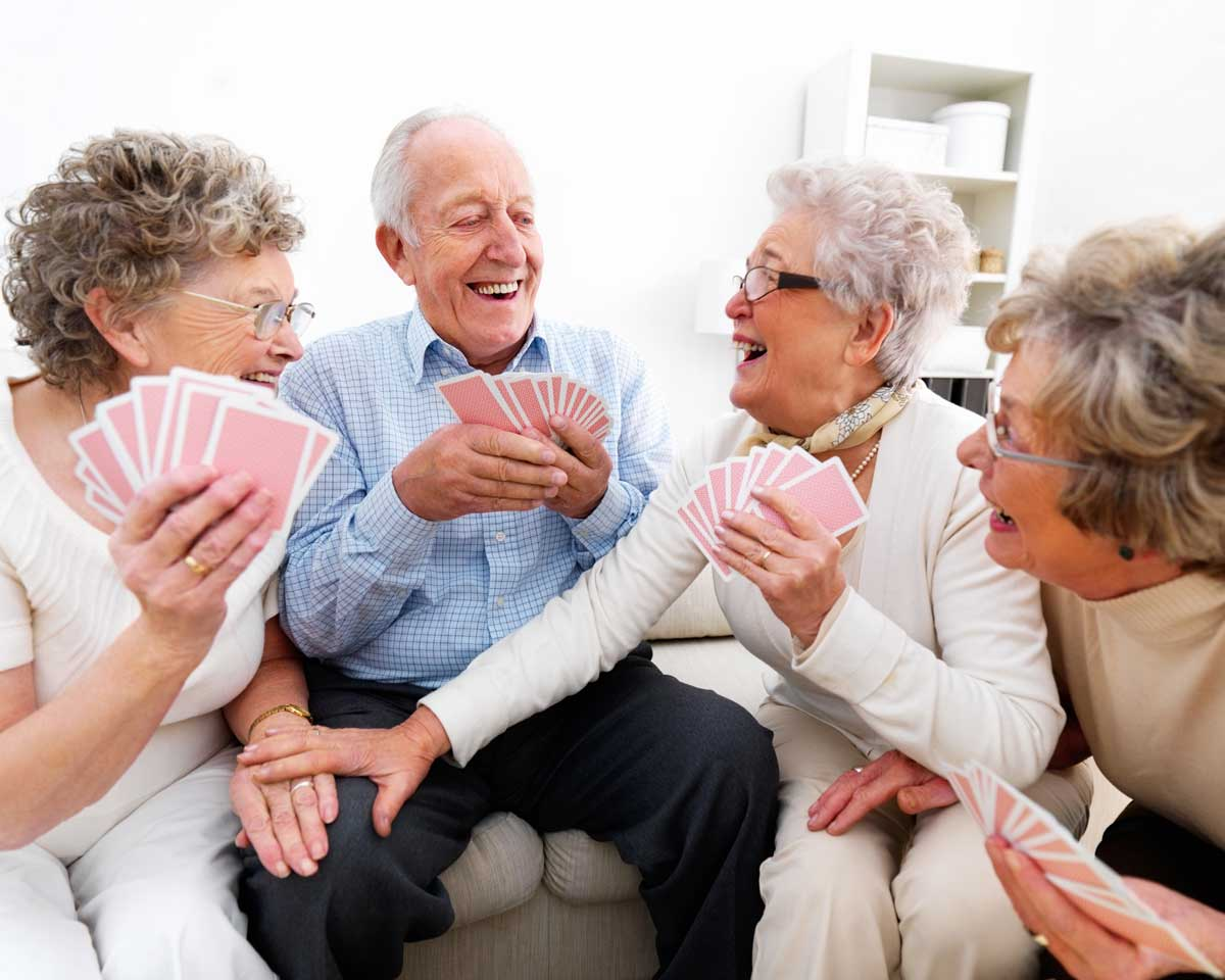 Four senior living residents sit together on a sectional couch and laugh over a game of cards