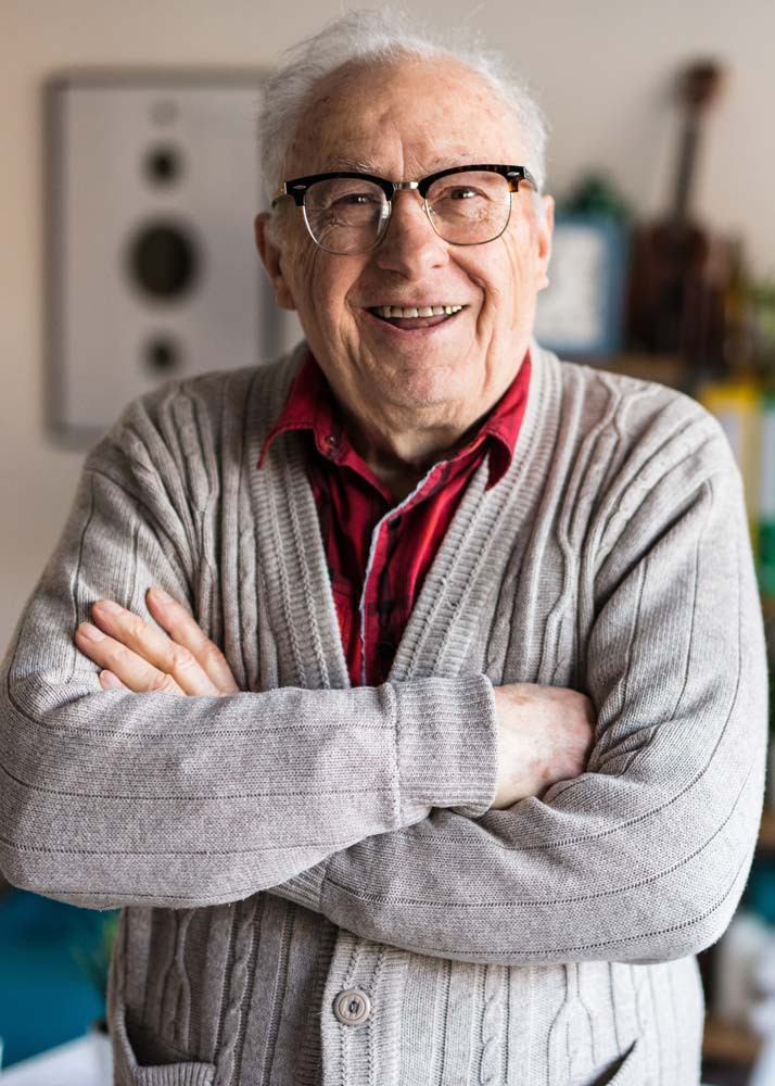 Older man wearing sweater and glasses smiles with arms crossed