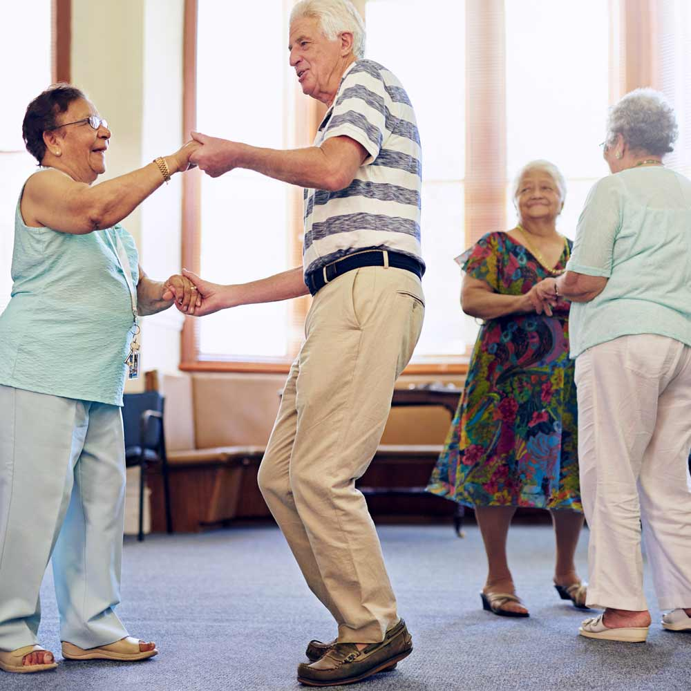 Assisted living residents participate in dance lessons in activity room