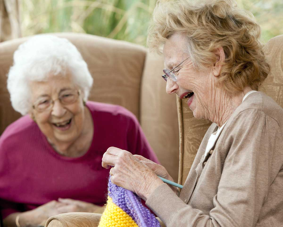 Two older women knit together and laugh while sitting on armchairs