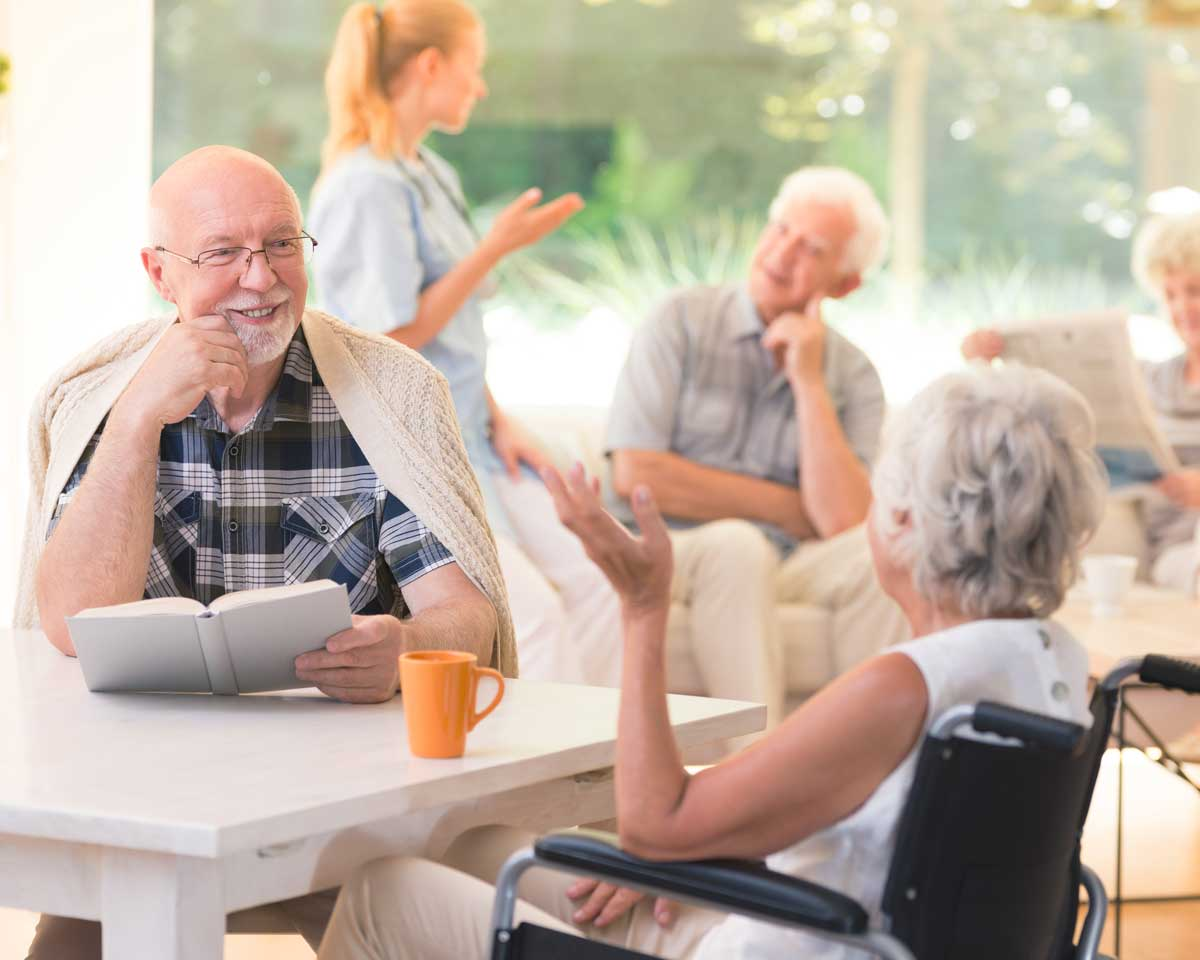 Older man and older woman in wheelchair sit at a table reading and chatting in activity room