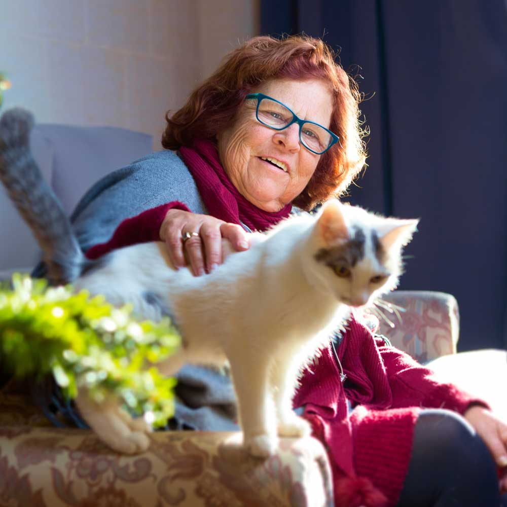 Female assisted living resident smiles and sits on couch while petting kitten