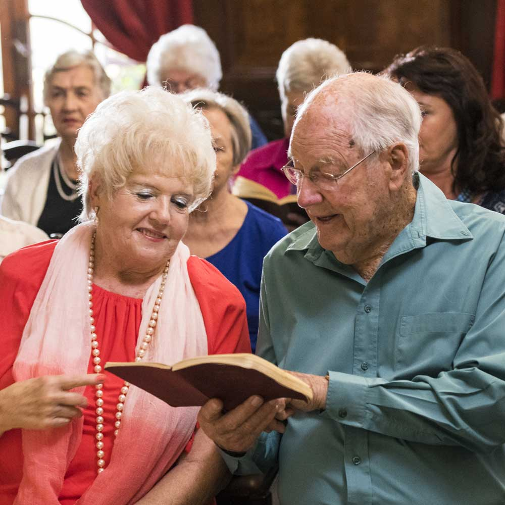 Older male and female resident sing from hymnal during worship service in chapel