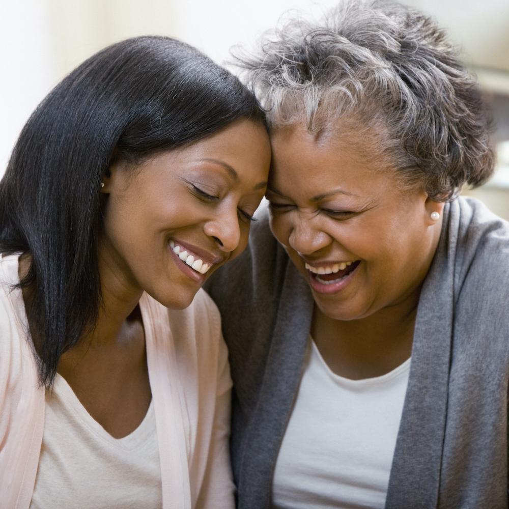 Young woman and female Grace House resident smile with eyes closed and foreheads touching