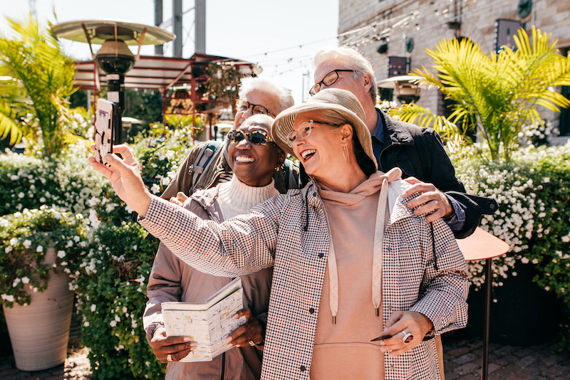 Diverse group of seniors stands in an outdoor garden area while one woman takes selfie of group on cellphone